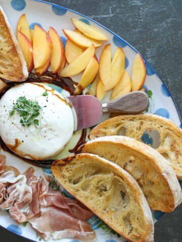 Prosciutto, peaches, burrata and crostini plate
