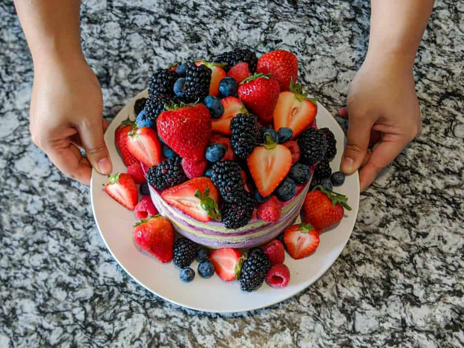 2 hand holding a white circle plate of a cake covered in fresh berries with a grey black marble background