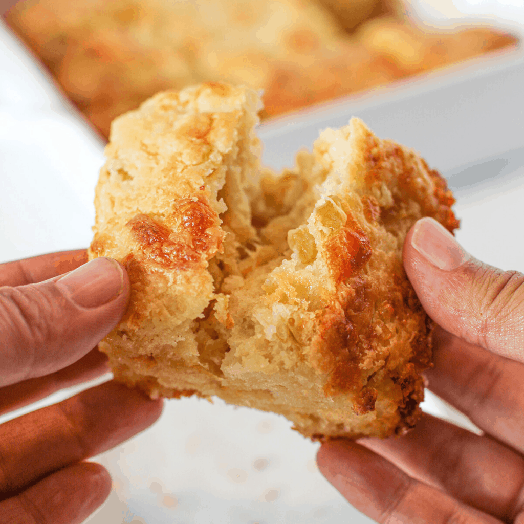 Hand opening a green chile cheddar biscuit and a square pan of the biscuits in the background
