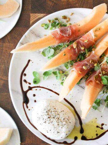 Crenshaw Melon, Burrata and prosciutto on a marble platter with wood cutting brown in the background, two plates off to the side