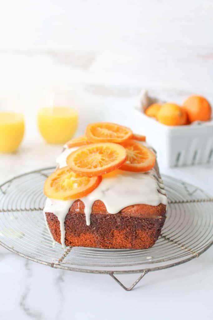 Yogurt Orange Juice Cake whole on cooling rack with OJ and mandarins in the back