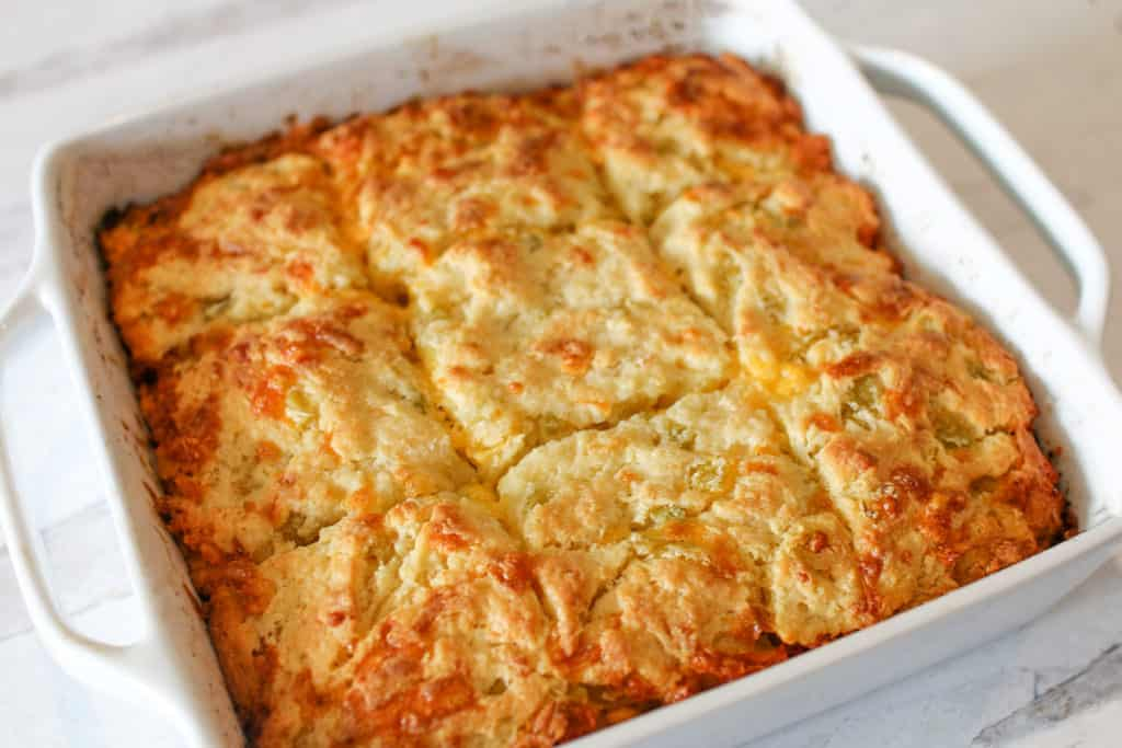 A square baking dish full of green chile cheddar biscuit cut into squares at an angle