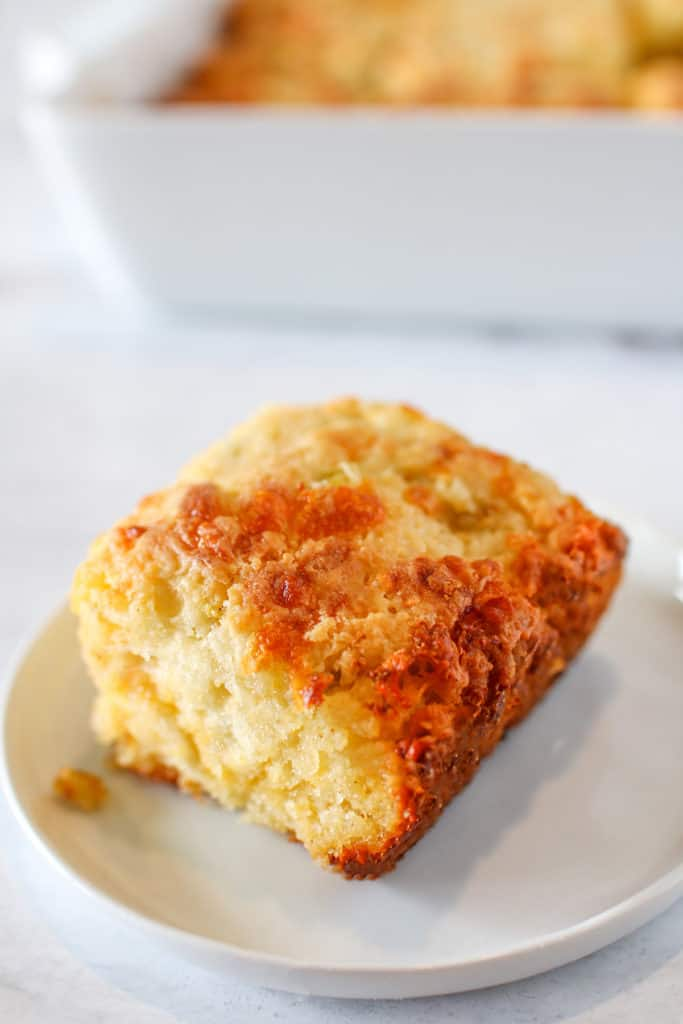 Green Chile Cheddar Biscuits on a small white plate with a baking pan in the background