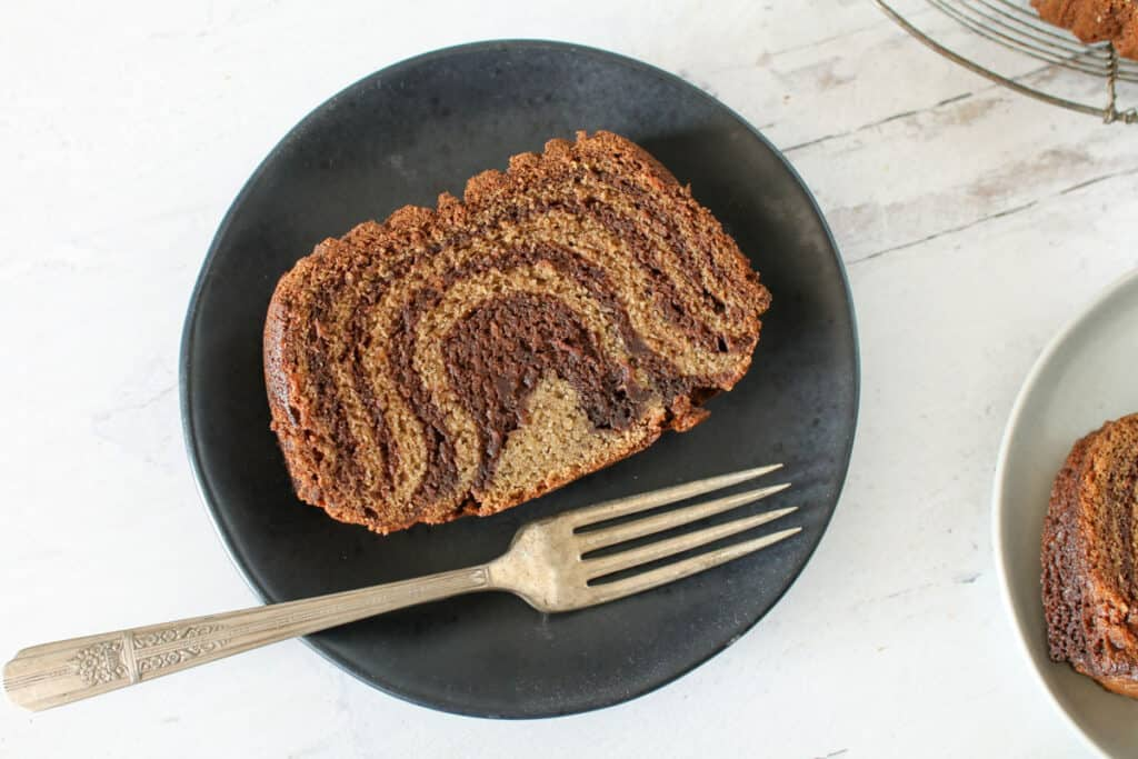 Slice of banana nutella bread on a place plate with an antique for off to the side of the plate