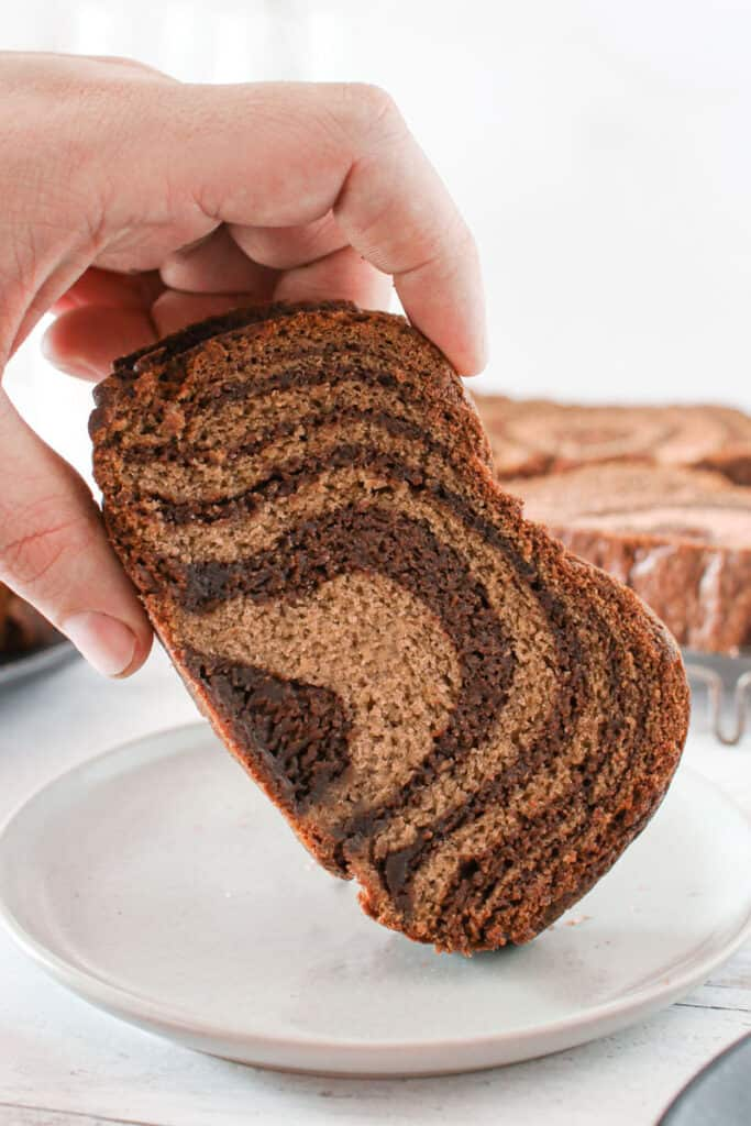 straight on photo of a slice of banana nutella swirl bread being picked up by a hand on a small white plate with more slices flat in the background