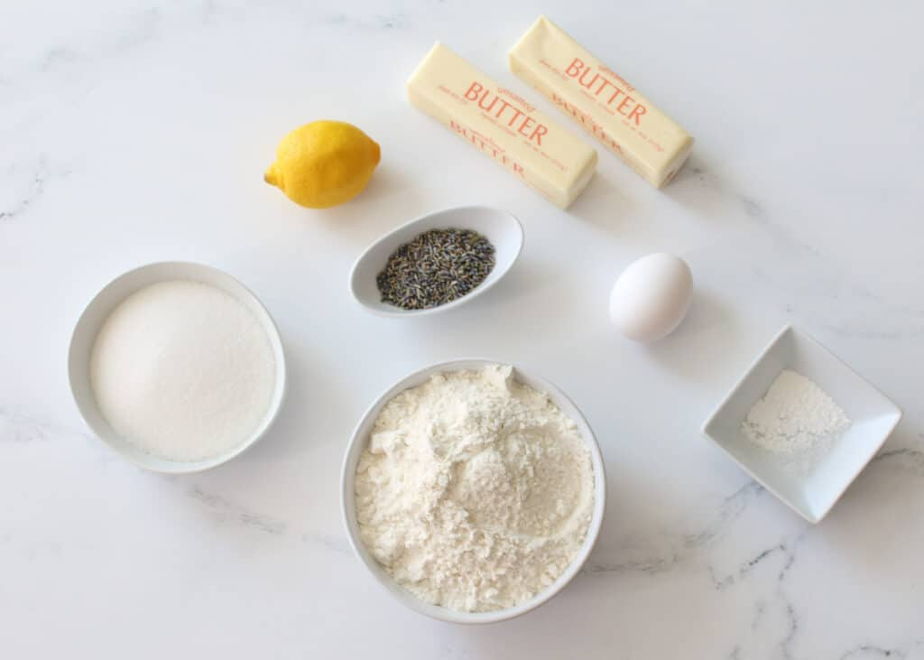 Lemon Lavender Cookie Bar Ingredients in different sized white bowls except for 1 whole lemon, 1 white egg, and 2 sticks of butter in the wrapping paper on a white marble background