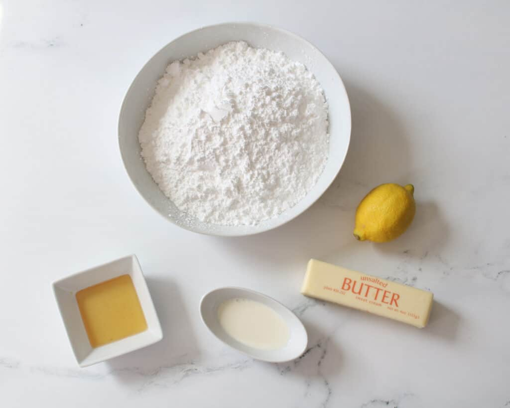 Lemon Honey Frosting ingredients in white bowls except for 1 whole lemon and 1 stick of butter in the originally wrapping