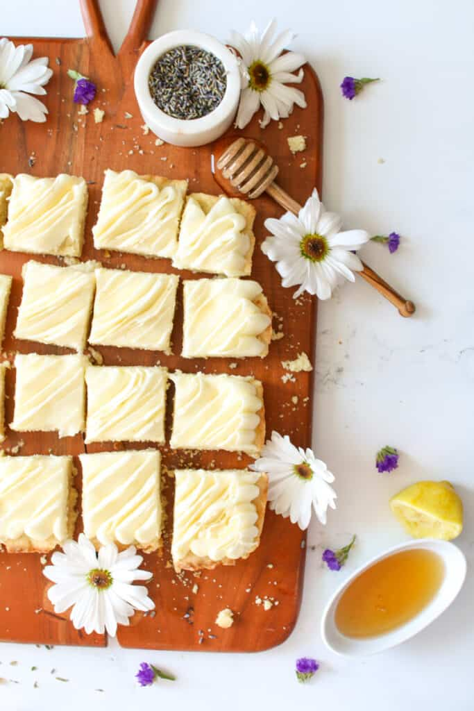 Lemon Lavender Cookie Bars cut into small squares on a wooden board but slightly cut off. Lavender in a small marble bowl is in the top right with a honey dipper and honey in a small bowl in the bottom right. White flowers, mini lavender flowers and crumbled bars are scattered all around the board and on the white marble background