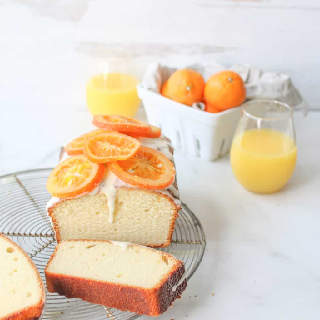 Orange Juice Yogurt Loaf sliced open on a cooling rack with 2 slices in front of it flat, 2 glasses of orange juice in small wine glasses and mandarins in a white berry basket with a grey linen in the backgorund