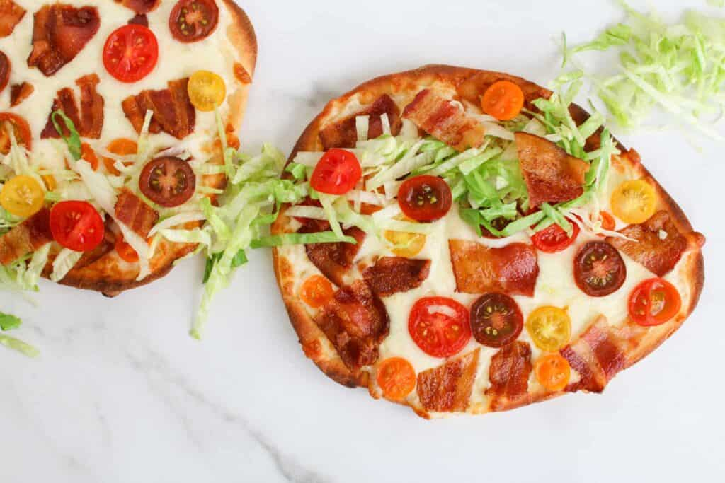 BLT Flatbread overnight with lettuce ribbon through 2 flatbread, white marble background