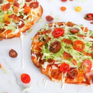 Angle of BLT Naan Flatbread with sauce, tomatoes and bacon surrounding