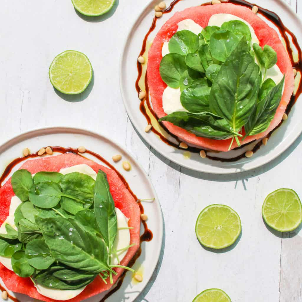 Overhead of two plated watermelon mozzarella salad with lime cut into circle surrounding the plates