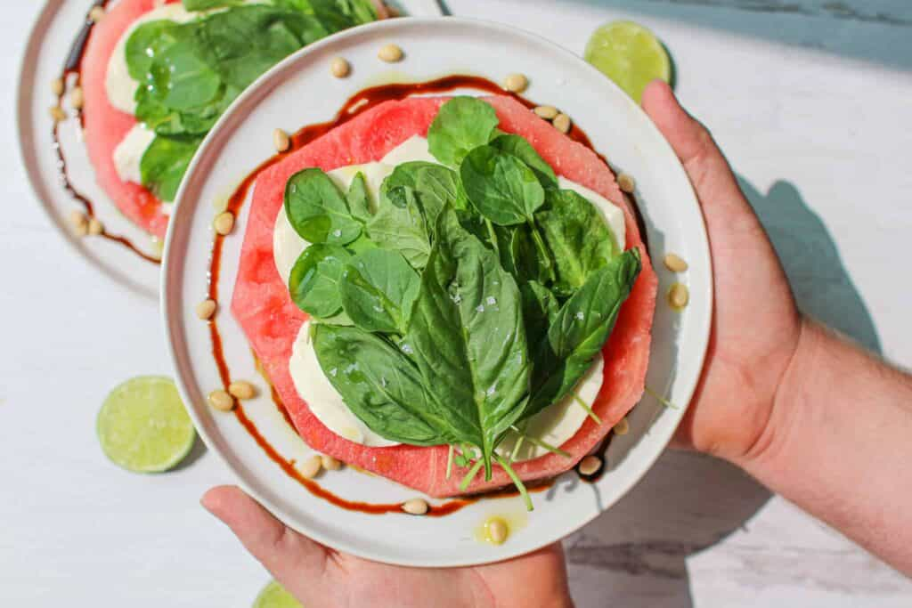 Overhead photo of Hand holding Watermelon Mozzarella Salad on a white plate, with one salad and limes sliced into circles in the background