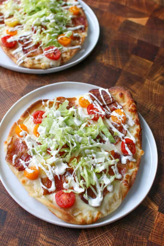 2 BLT Naan Flatbread on a white plates on a wood cutting board background