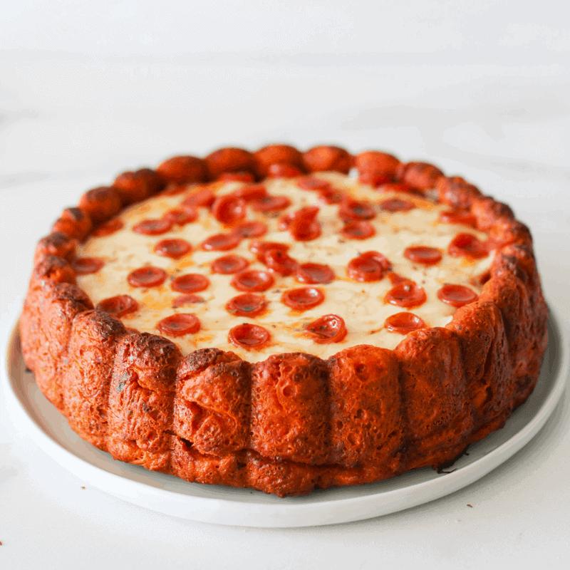 Straight on of whole Mozzarella Stuffed Pizza Cake on a medium circle plate topped with mini pepperoni