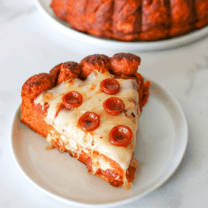 A slice of mozzarella stuffed pizza cake on a small circle plate with 5 mini pepperonis with the cake in the background