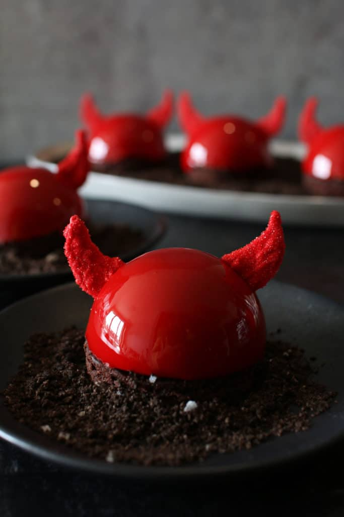 Straight on photo of halloween nutella devil entremet on a black plate, a gray plate has 3 entremets and another entremet on the black plate are in the background. everything sits on a black background and there is a dark grey back
