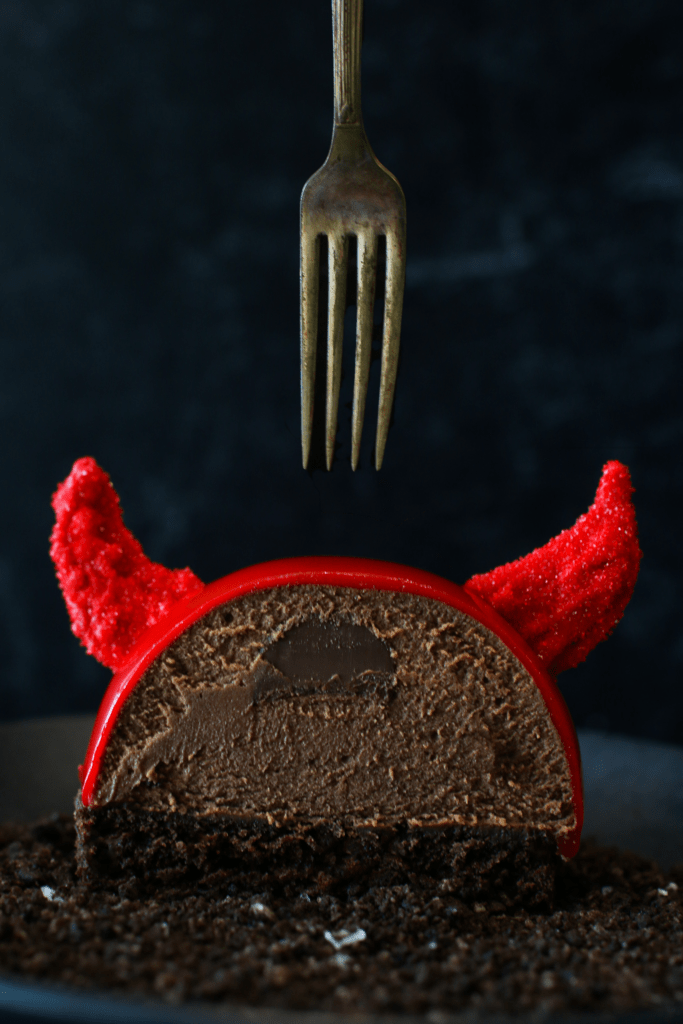 Straight close up on cross-section of a Halloween Nutella Devil Entremet with a fork above. There is a nutella filling surrounded by chocolate nutella mousse semisphere sitting on a cake round of devils food with red glaze and 2 red candy melt horns
