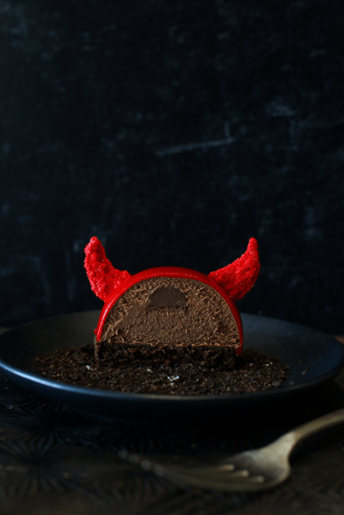Straight on cross-section of a Halloween Nutella Devil Entremet with a fork in from the plate. There is a nutella filling surrounded by chocolate nutella mousse semisphere sitting on a cake round of devils food with red glaze and 2 red candy melt horns. It sits on a black plate on a dark starburst bottom with a black background