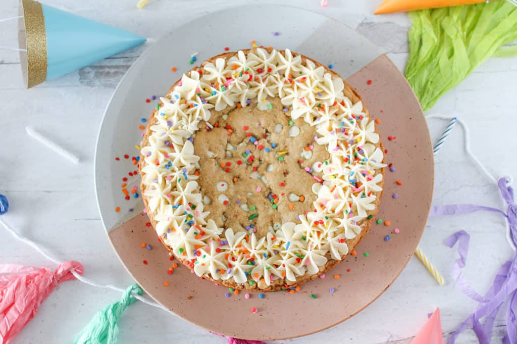 Overhead of Funfetti Chip Cookie Cake topped with buttercream and sprinkles on a white pink, white, grey platter with party decorations surrounding it