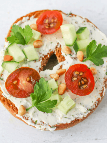 A toasted whole wheat bagel with Tzatziki Feta Cream Cheese Spread topped with sliced cherry tomatoes, diced cucumbers, toasted pine nuts and italian parlsey leaves