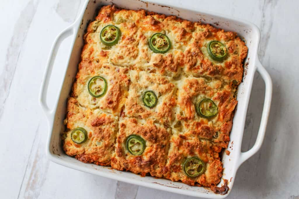 Cheesy Jalapeño Bacon Butter Swimming Biscuits in a 9x9 white square pan