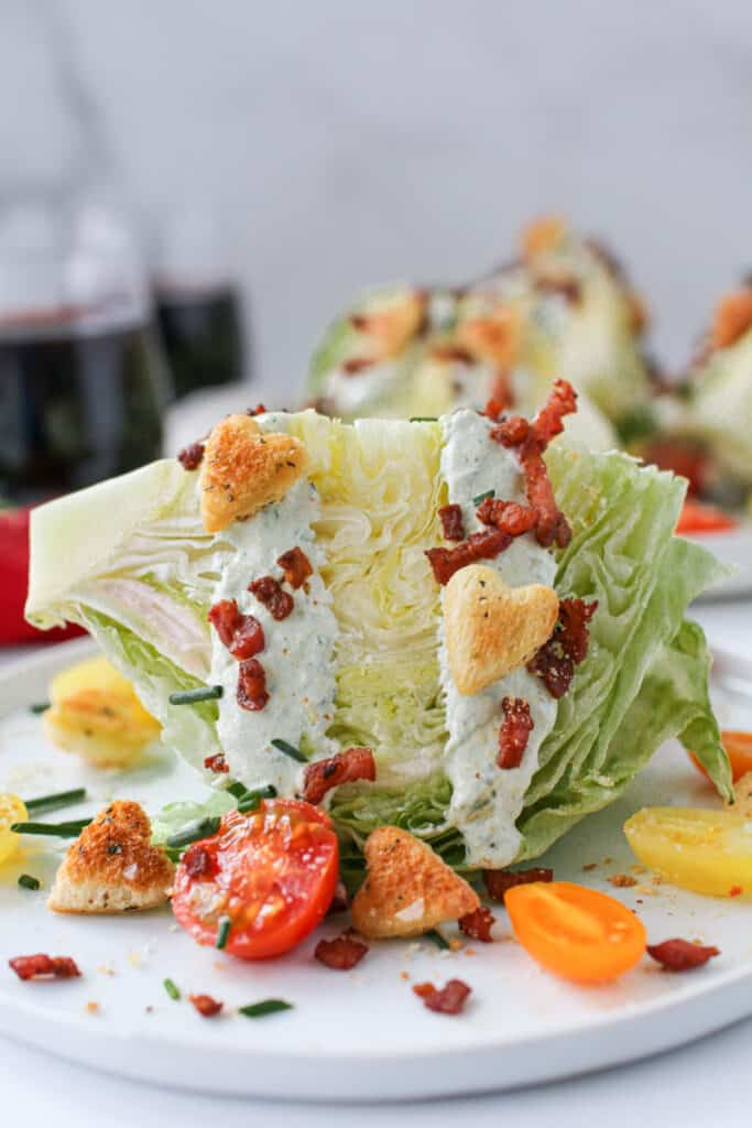 Straight on photo of 1 BLT Wedge Salad with Heart Croutons with more salads and 2 wine glass full of red wine in the background