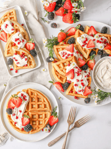"""Overhead of 3 white plates with waffles, berries and mascarpone cream. To the right there's a large white platter with a small bowl with mascarpone cream with a spoon, to the left is a rectagnle plate with waffles cut into 1/4 and below a smaller circle plate with a whole waffle. slightly to the bottom right are 2 antique forks making an """"x"""" shape and a grey linen cloth behind 2 plates to the left and top middle is a berry basket with mixed berries and small white flowers scatter everywhere"""