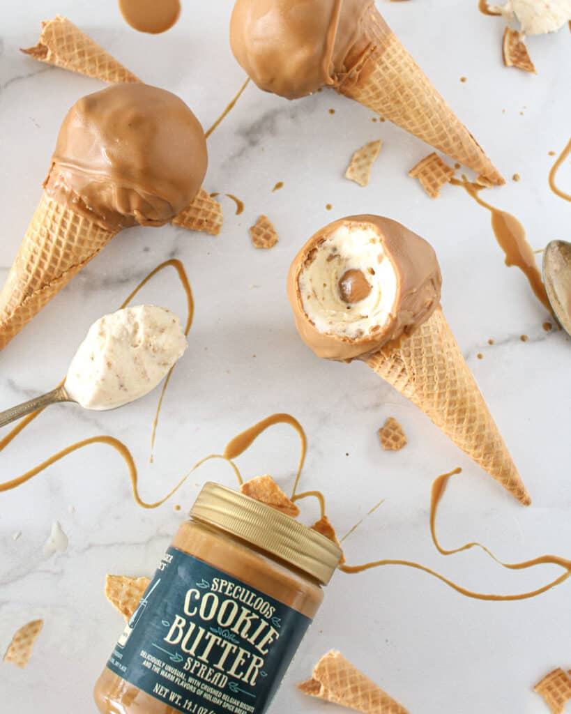 Overhead of cookie butter drumsticks with 1 slightly open and 2 whole, along with a jar of cookie butter open