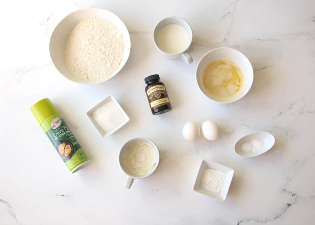 Ricotta Vanilla Bean Waffle Ingredients spread across a white marble background in small white bowls and mugs in various sizing plus a can of non stick spray in a green can of nonstick spray to the left and the bottle of vanilla bean paste in the center