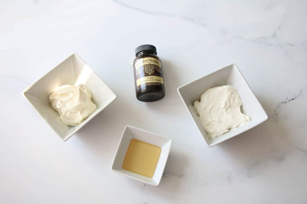 Overhead of mascarpone ingredients divided into small square bowls except for the vanilla bean paste which is in a brown bottle