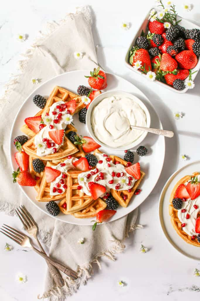 """Overhead of ricotta vanilla bean waffles cut into ¼ circles, stacked on top of each other to the left of the platter, topped with dollops of mascarpone cream and mixed berries, to the right is a small bowl full of mascarpone cream with an antique spoon. It sits on top of a grey linen napkin on a white marble background with a white berry basket off to the right and a small white plate with a whole waffle off the the bottom right corner. Small white flowers are scattered about and 2 antique forks forming an """"x"""" are to the bottom left of the platter"""