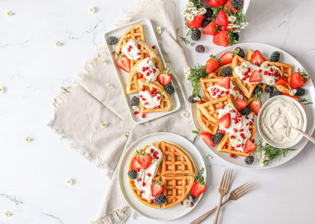 """Overhead of 3 white plates with waffles, berries and mascarpone cream. To the right there's a large white platter with a small bowl with mascarpone cream with a spoon, to the left is a rectagnle plate with waffles cut into ¼ and below a smaller circle plate with a whole waffle. slightly to the bottom right are 2 antique forks making an """"x"""" shape and a grey linen cloth behind 2 plates to the left and top middle is a berry basket with mixed berries and small white flowers scatter everywhere"""