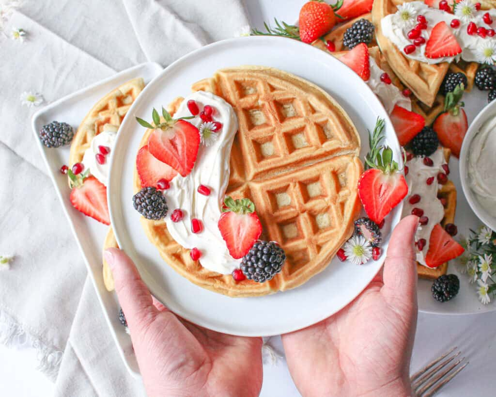 Whole ricotta vanilla bean waffle on a small plate with a swoosh of mascarpone cream on top of the left part of the waffle with some mixed berries and 2 hand holding the plate from the bottom with thumbs up. Behind it are a large white platter and rectangle plate full of more waffles, berries and cream sitting on a grey linen