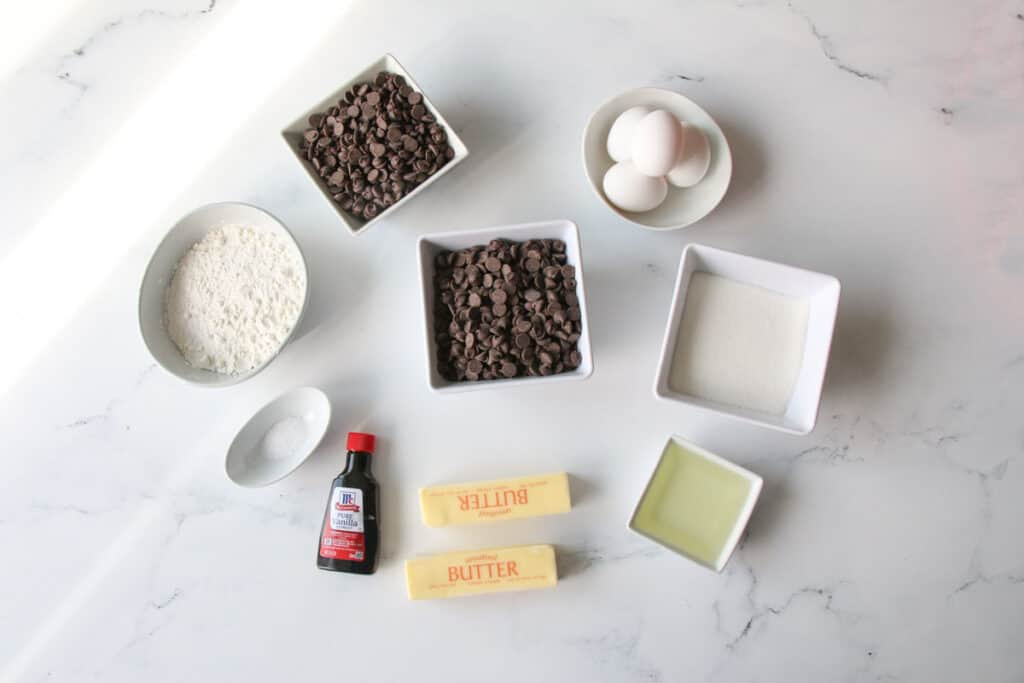 Fudgy Brown Butter Brownies ingredients on a flat lay. Ingredients in differently shaped bowls and plates with the 2 sticks of butter in its normal packaging and a small bottle of vanilla extract