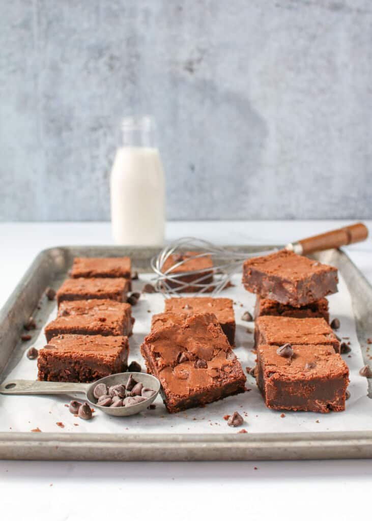 Angled straight on photo of fudgy brown butter brownies on a silver baking tray lined with parchment papper with a few brownies stacked or leaning on each other. Scatter chocolate chips with a few in an antique tablespoon, and an antique whisk with wooden handle in the background. In the very back is a full milk bottle full of milk of a grey background