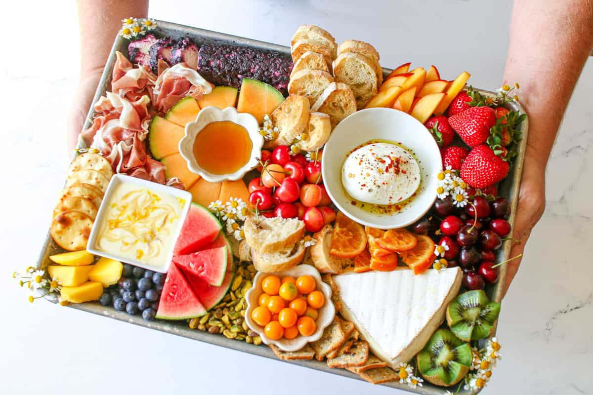 The Trader Joe's Summer Fruit & Cheese Board being held in two hands at an angle on a white marble background.