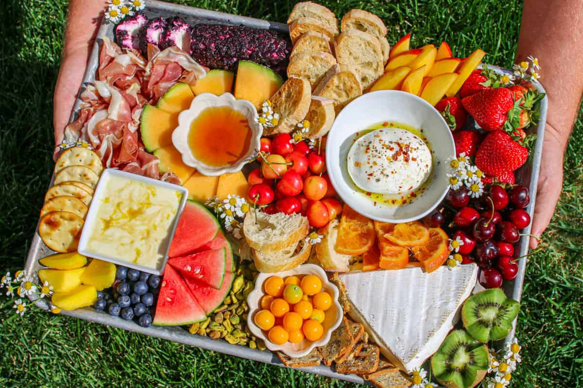 Trader Joe's Summer Fruit & Cheese Board being held in two hands outside by green grass