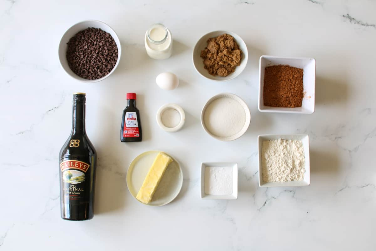 Overhead of ingredients on a white marble background. In the top right lert are a bowl of mini chocolate chips, next tot it on the right is a milk bottle of heavy cream, underneath is a single egg, next to it is a small white bowl of brown sugar and next to it is a small white square bowl with cocoa powder. In the middle row starting from the left is a small bottle of vanilla extract, a very small bowl of kosher salt, next to it is a small white bowl of granulated sugar. Finally, on the bottom left row is a full bottle of  Bailey's Irish cream, next to it is a small white plate with a stick of butter, next to it is a small white square bowl with baking soda and finally next to a small square white bowl with all purpose flour.