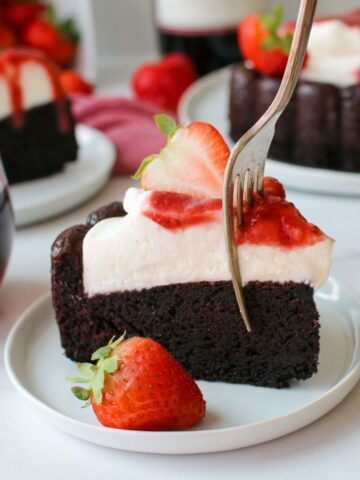 a slice of leftover red wine chocolate cake with mascarpone whipped cream and strawberry red wine sauce with three drizzles over the side, topped with a strawberry sliced in half and a fork in the cake taking to get a piece