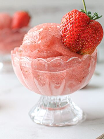 Scoop of strawberry rose sorbet in a glass ice cream bowl topped with a whole strawberry on a white marble background