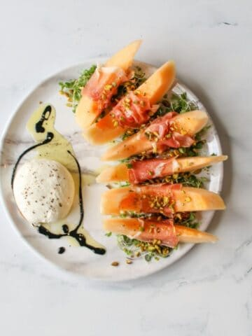There is a large white circle platter on a marble background with micro greens to the right with 6 slices of crenshaw melon with a slice of prosciutto wrapped around the middle of each slice and pistachios on top and a splash of olive oil to the left of the platter with a large ball of burrata on top with a drizzle of balsamic glaze surrounding it. Salt and pepper are also on everything on the platter.