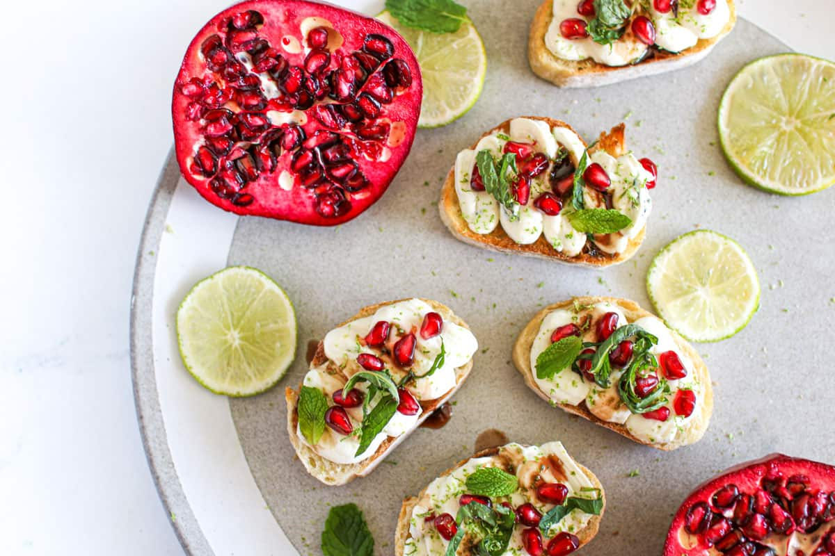 Crostini with lime whipped goat cheese and pomegranate on a grey speckled plate with sliced lime and pomegranates sliced in half